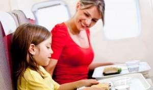 mother_and_son_having_a_meal_in_the_airplane_while_flying_shutterstock_96816280