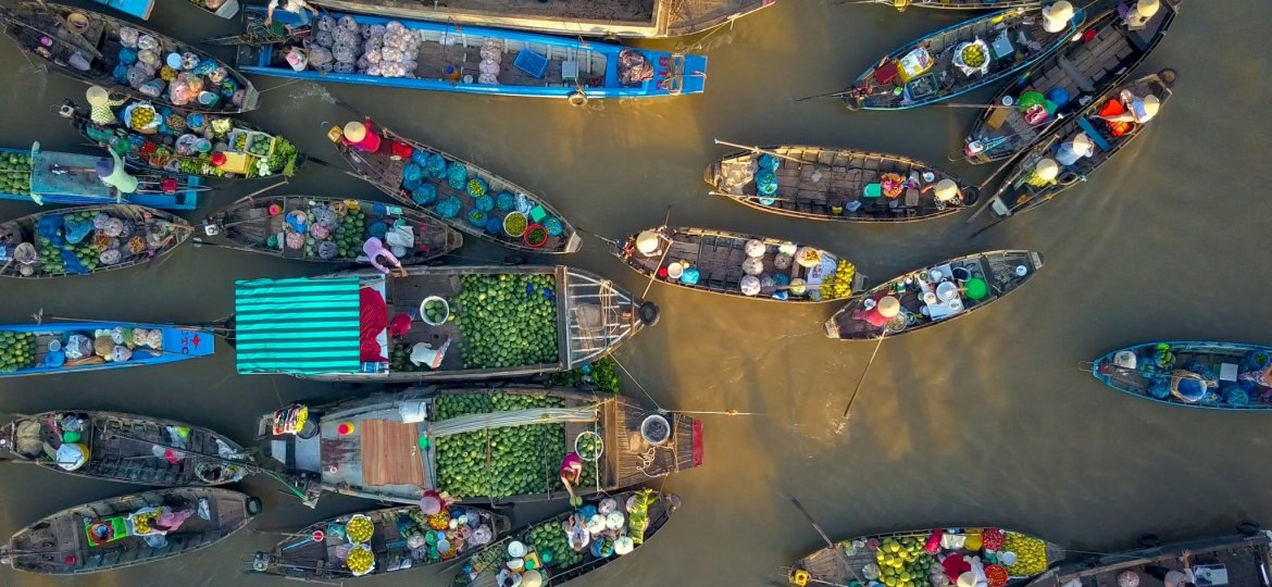 AERIAL: Local people buying and selling colorful produce from wooden boats.
